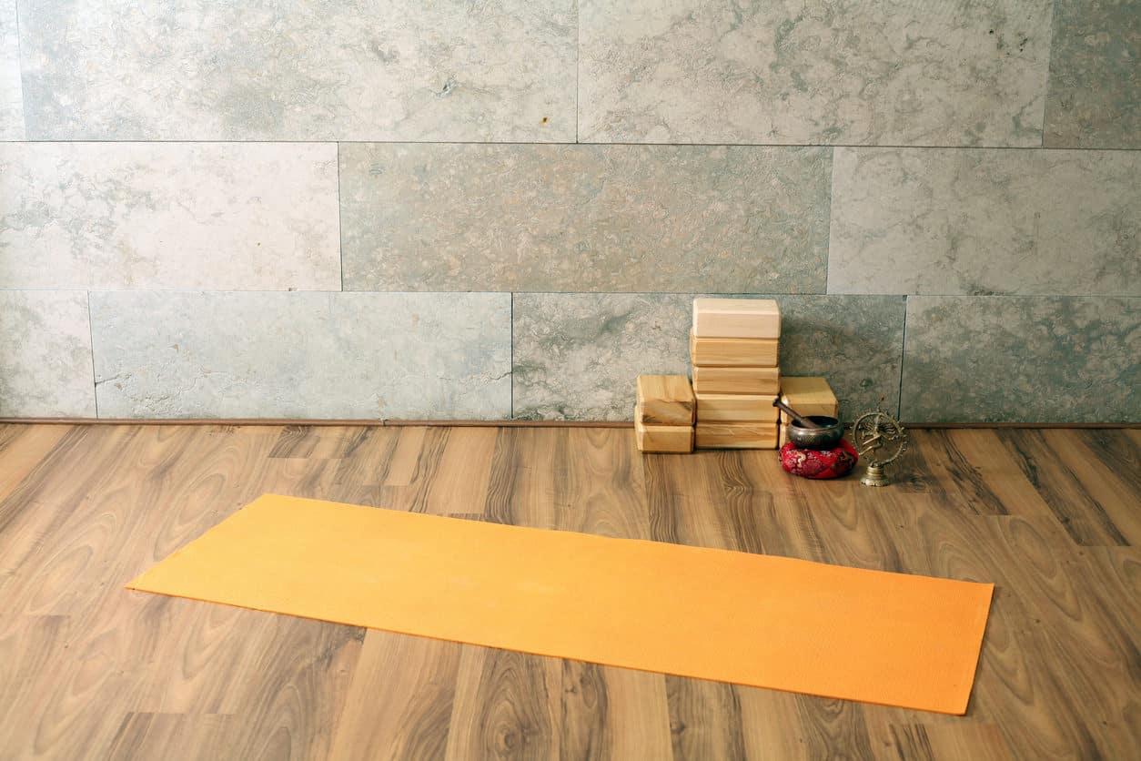 Yoga studio with wood floor and stone wall.