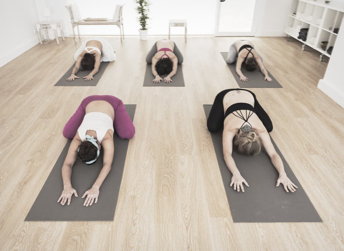 Small yoga studio design with light wood flooring, white walls, plant and yoga gear shelving.