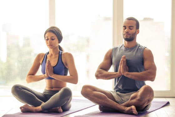 Woman and man doing yoga in yoga clothing in a yoga studio
