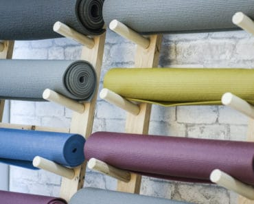 Different types of yoga mats stored on yoga mat shelf