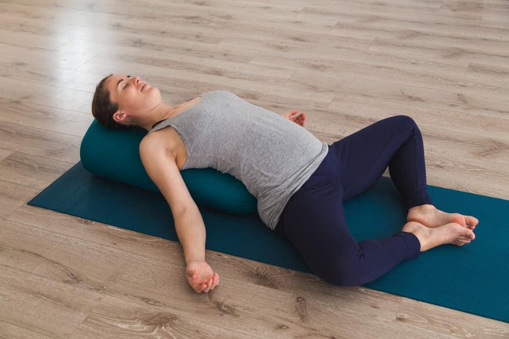 Woman doing yoga with bolster