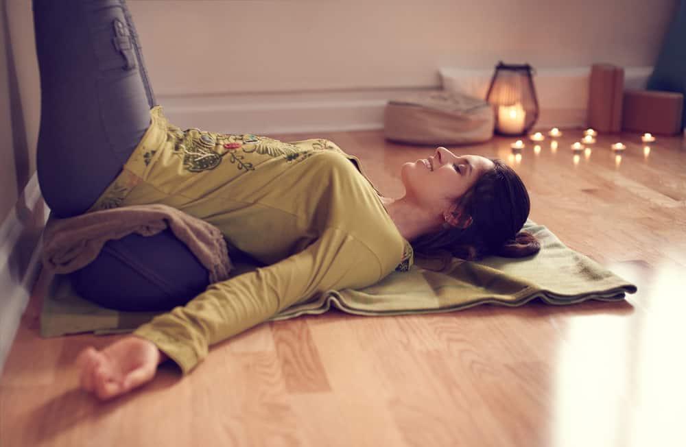 Woman lying on yoga blanket in studio