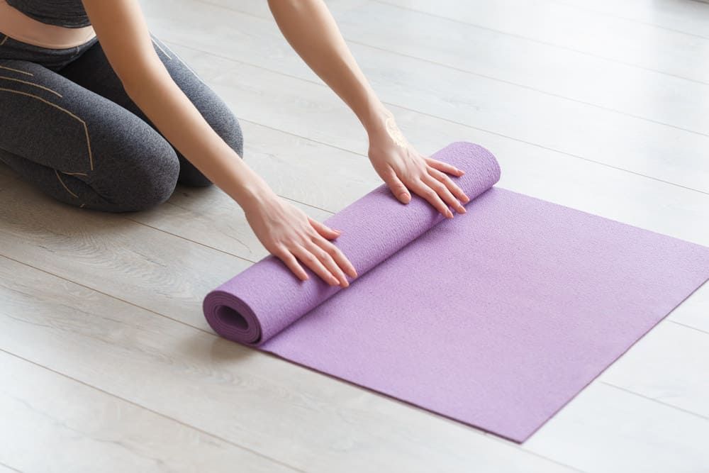 Yoga mat being rolled up in yoga studio