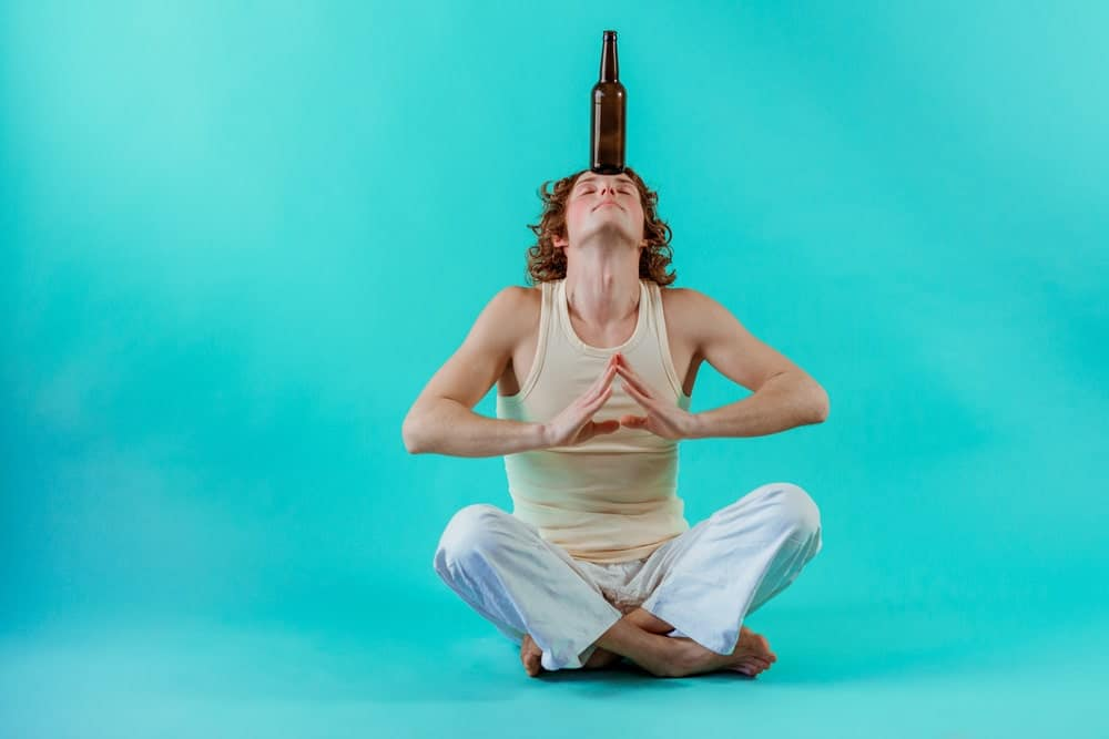 Young man doing yoga with a bottle of beer