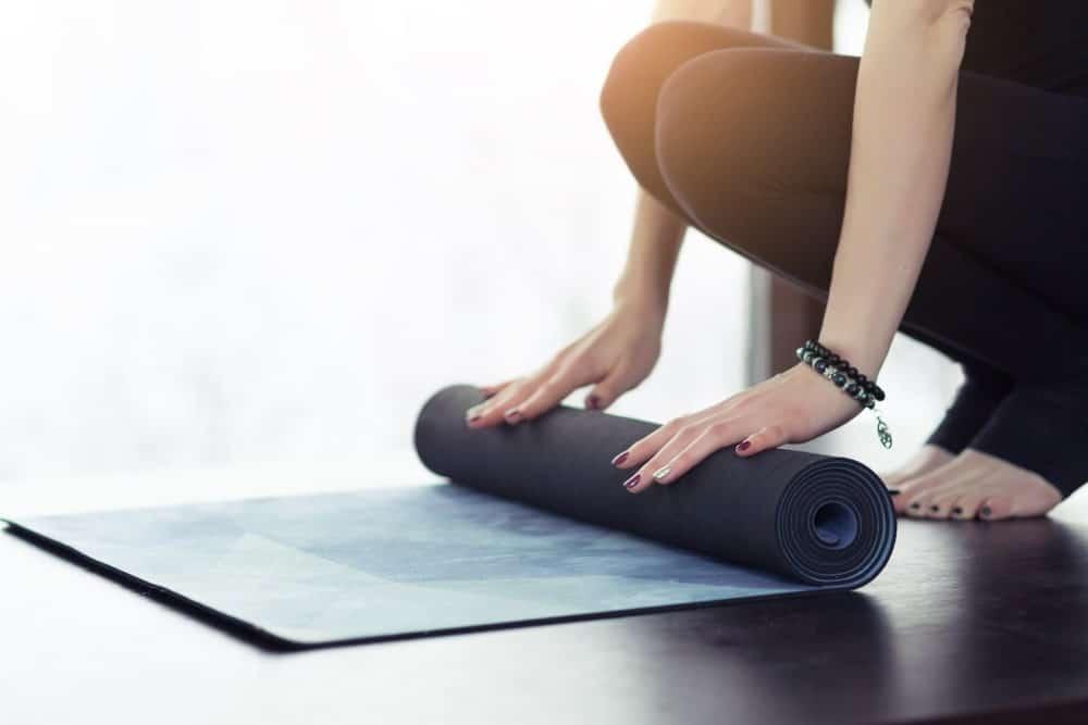 A woman rolling a yoga mat