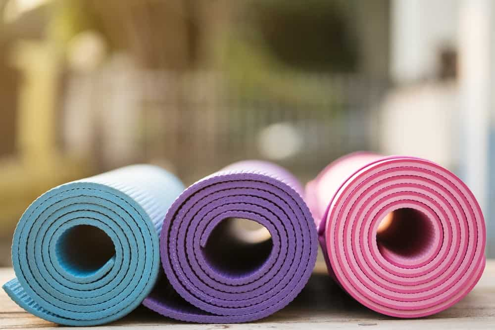 Three folded yoga mats on a table