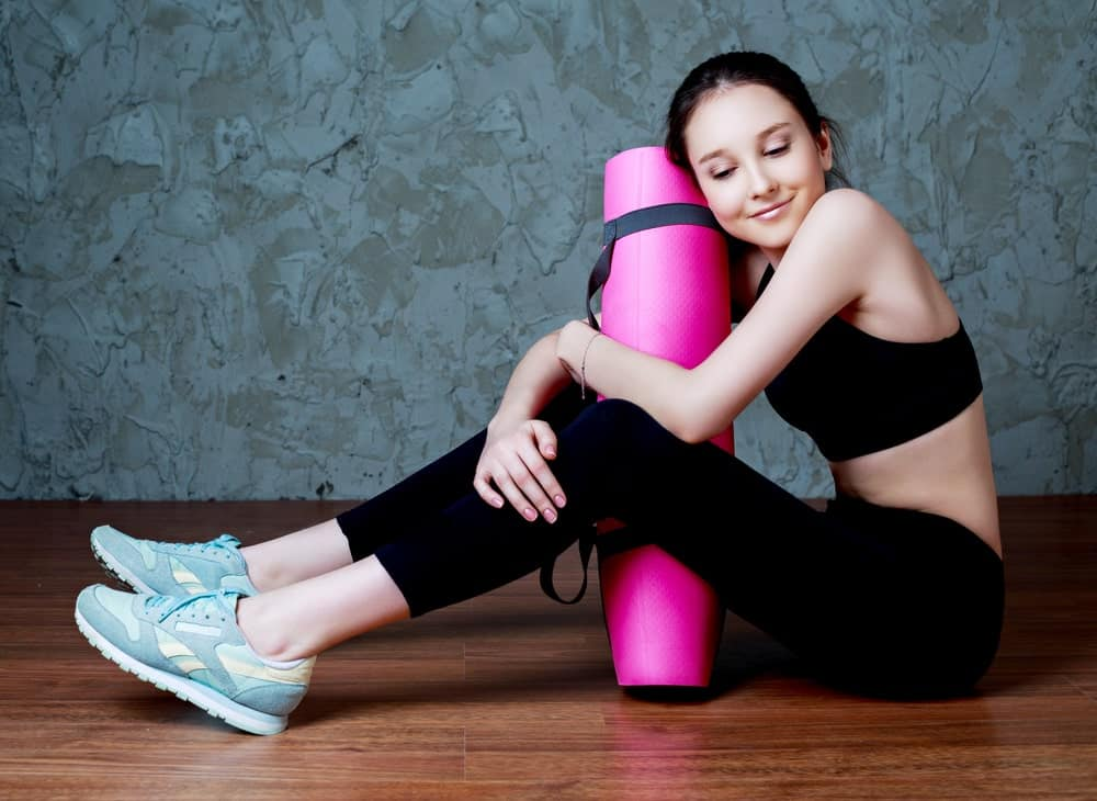 A girl hugging her yoga mat
