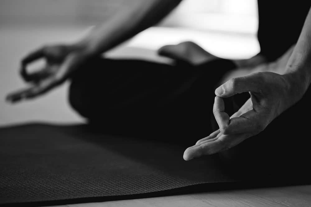Black and white picture of a man practicing yoga on a mat