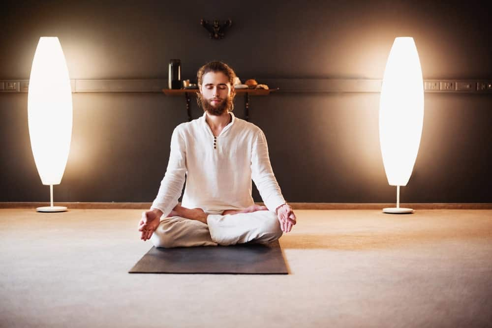A man practicing yoga between a pair of floor lamps.