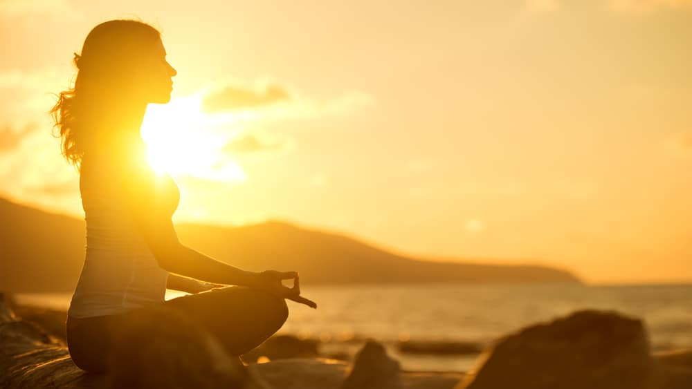 Girl meditating at the beach with beautiful sunset behind her