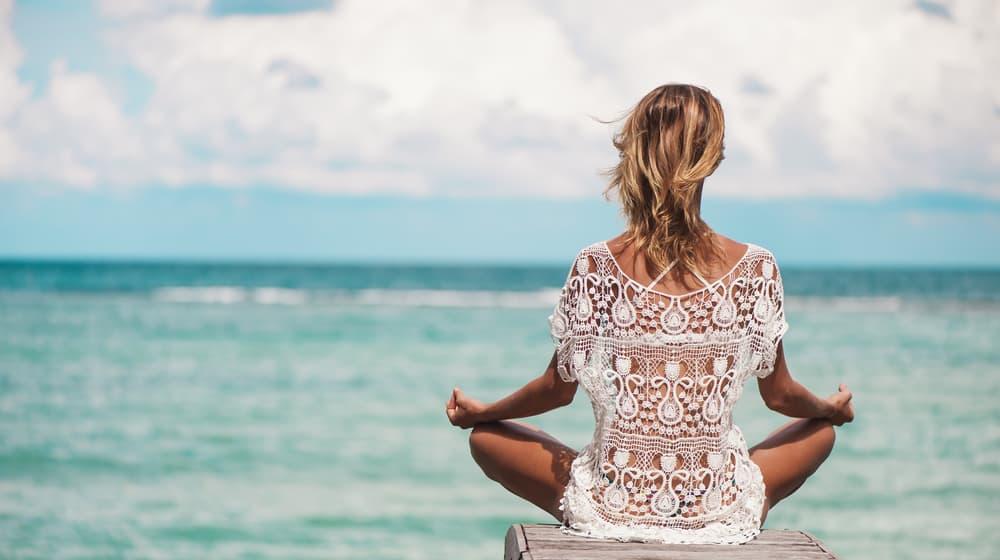 Girl sitting on pier meditating wearing white see through dress