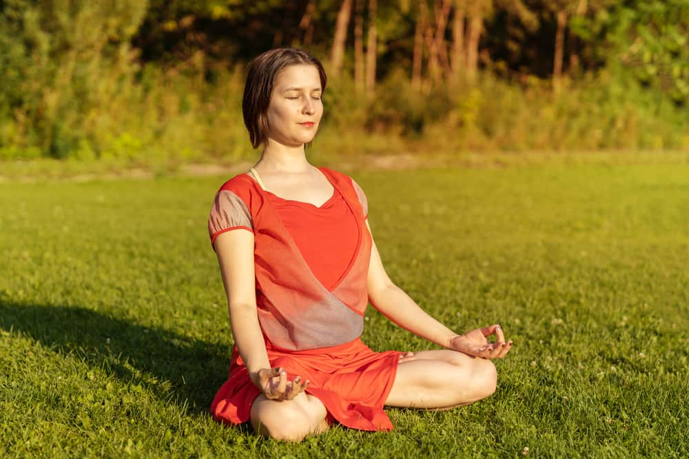 Girl meditating in a red dress sitting on grass in evening time