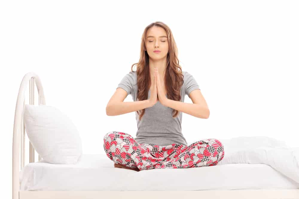 Girl meditating in her pajamas on the bed