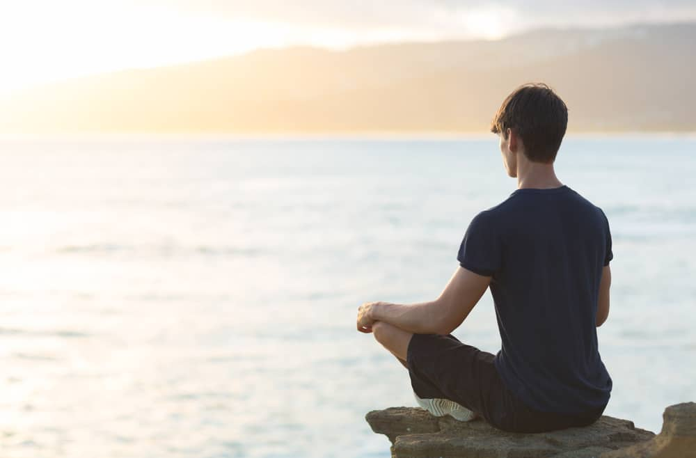 Boy in blue shirt meditating on edge of cliff in front of water