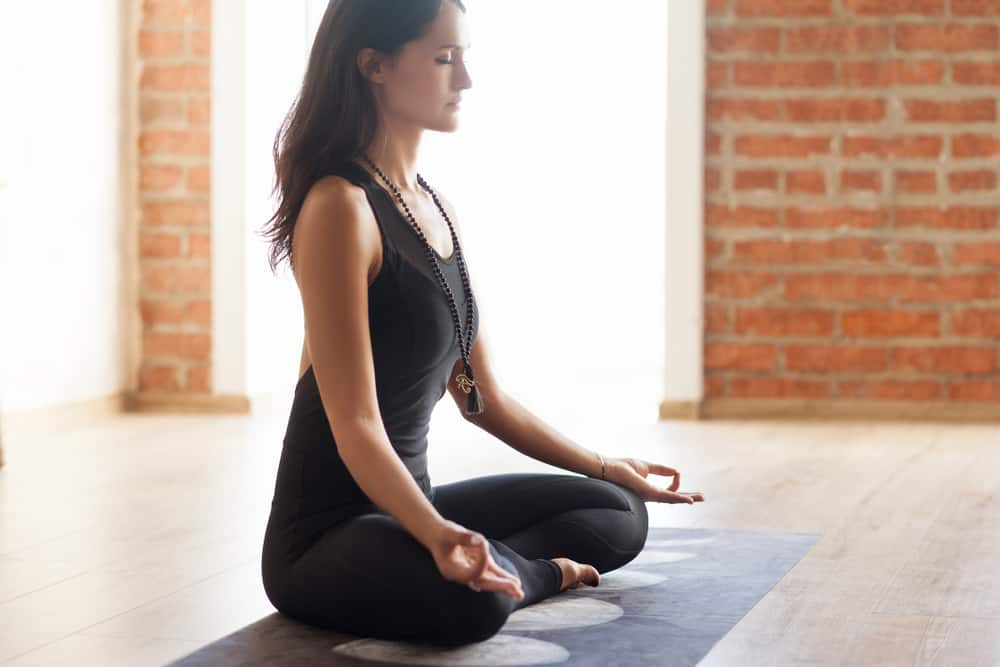 Girl dressed in black yoga clothes peacefully meditating in lotus position
