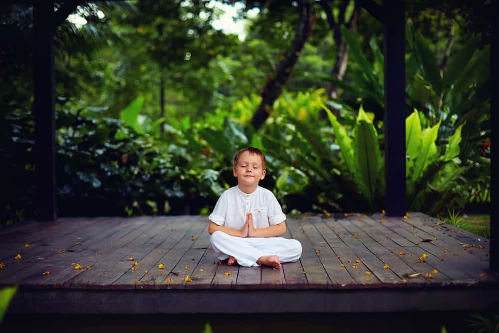 Little boy sitting on wooden paltform meditating in park