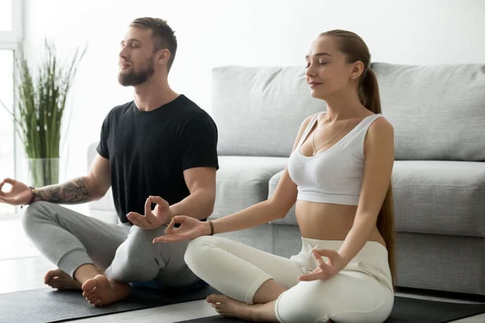 Couple practicing breathing pranayamas