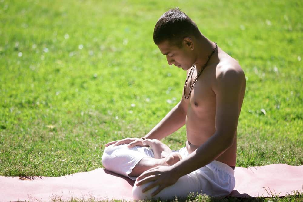 man practicing yoga outdoors