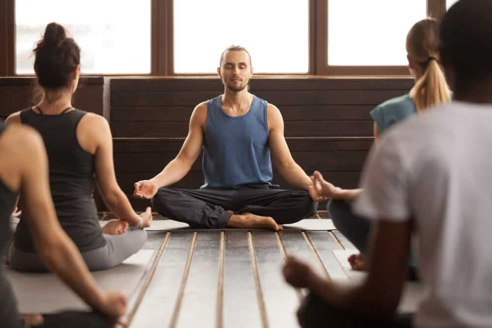 Male Yoga instructor teaching a group of students.