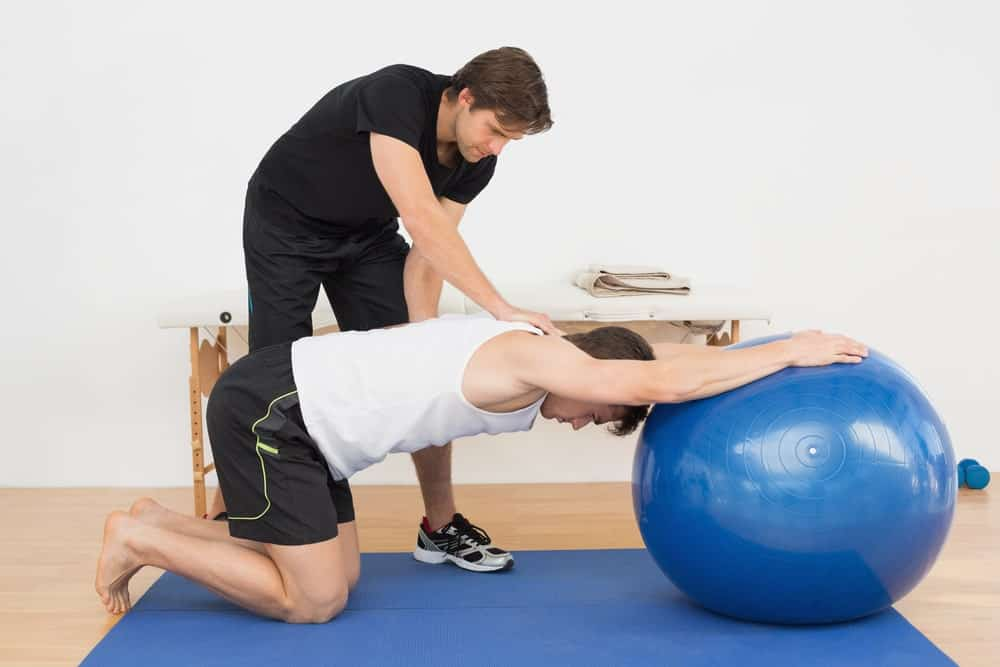 Instructor holding down a man posing with a balance ball.