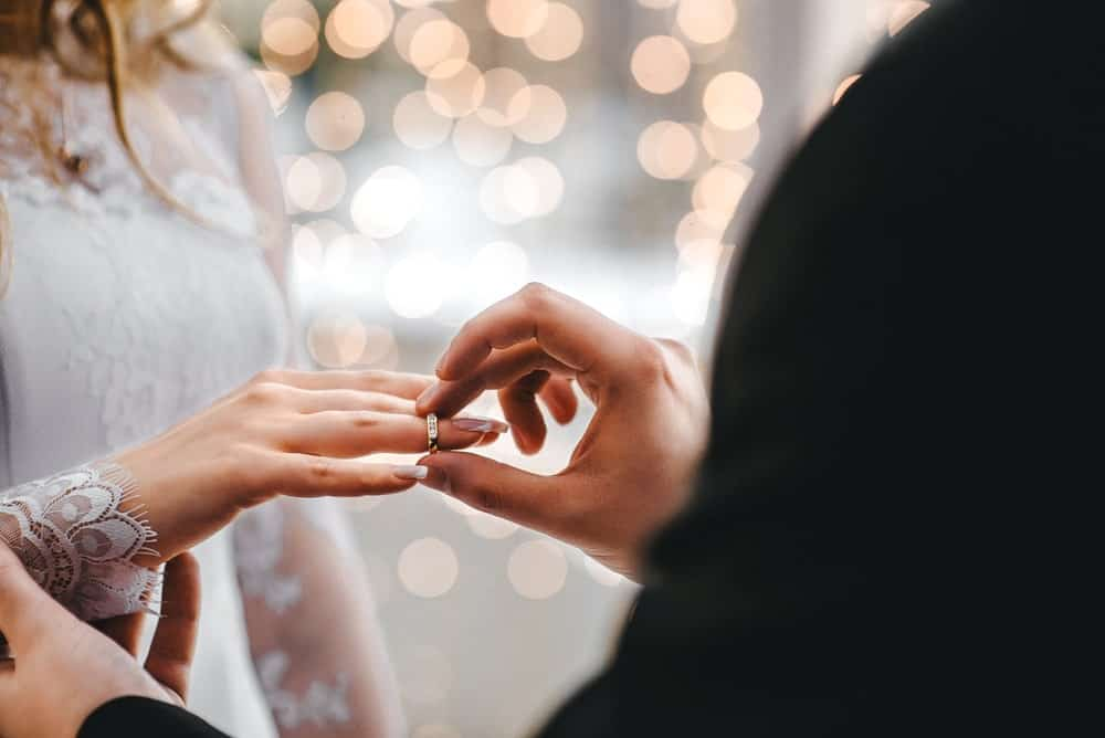 Couple exchanging wedding rings at a ceremony.