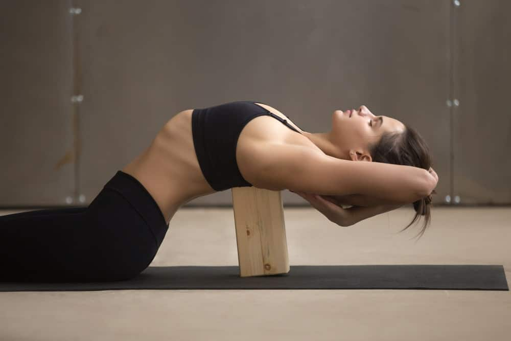 Woman bending backward using a yoga block.