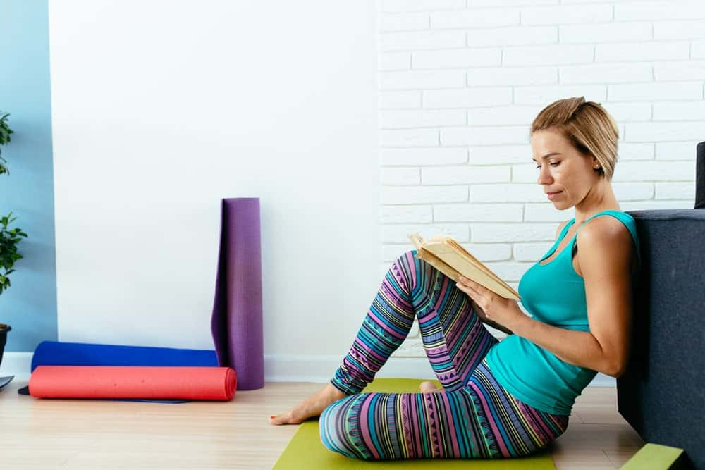 Woman reading a book on a yoga mat.
