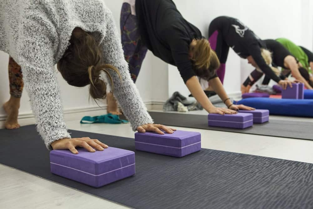 Women stretching downward using yoga blocks.