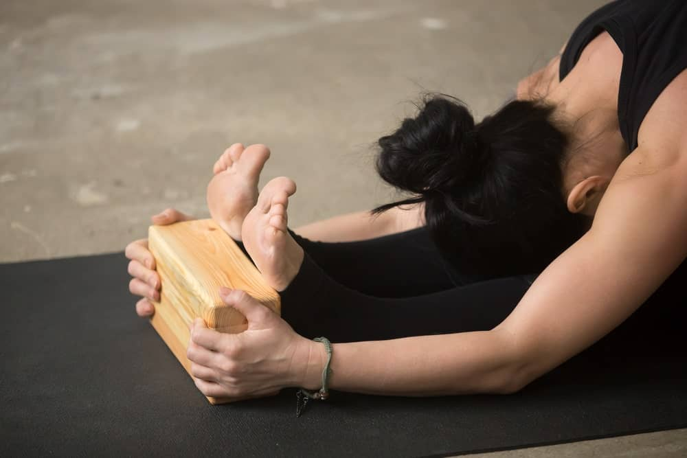Woman stretching using a yoga block.