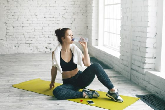 A girl sitting on a yoga mat drinking water from a bottle.