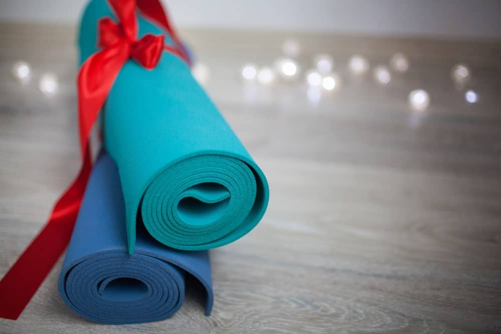 Rolled Manduka mats with a red ribbon