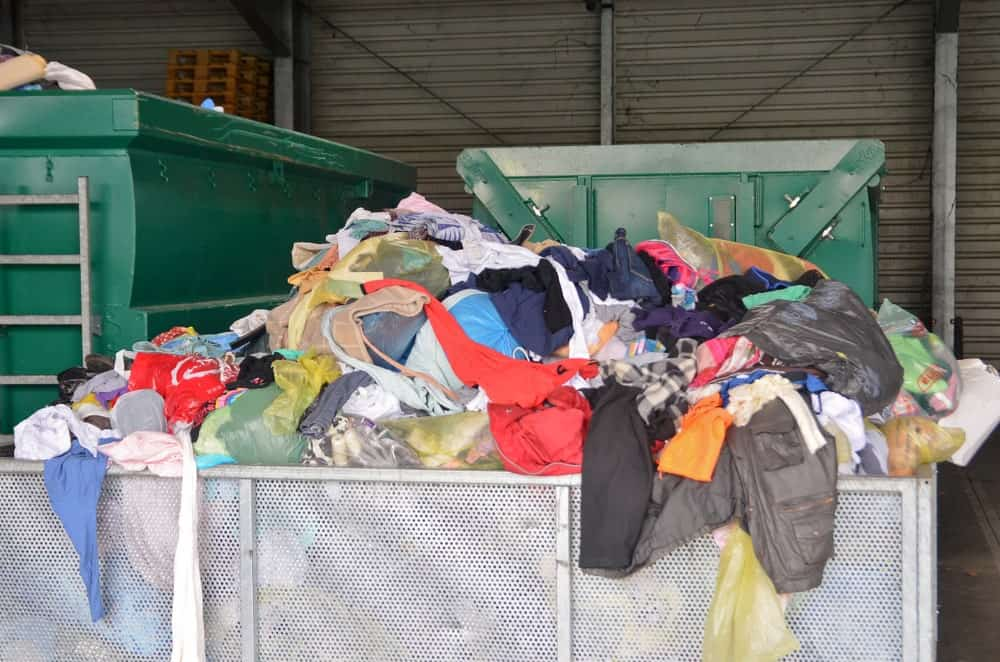 A pile of used clothes in a large metal storage in a warehouse.