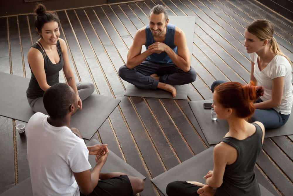 Yogis sitting on Manduka mats