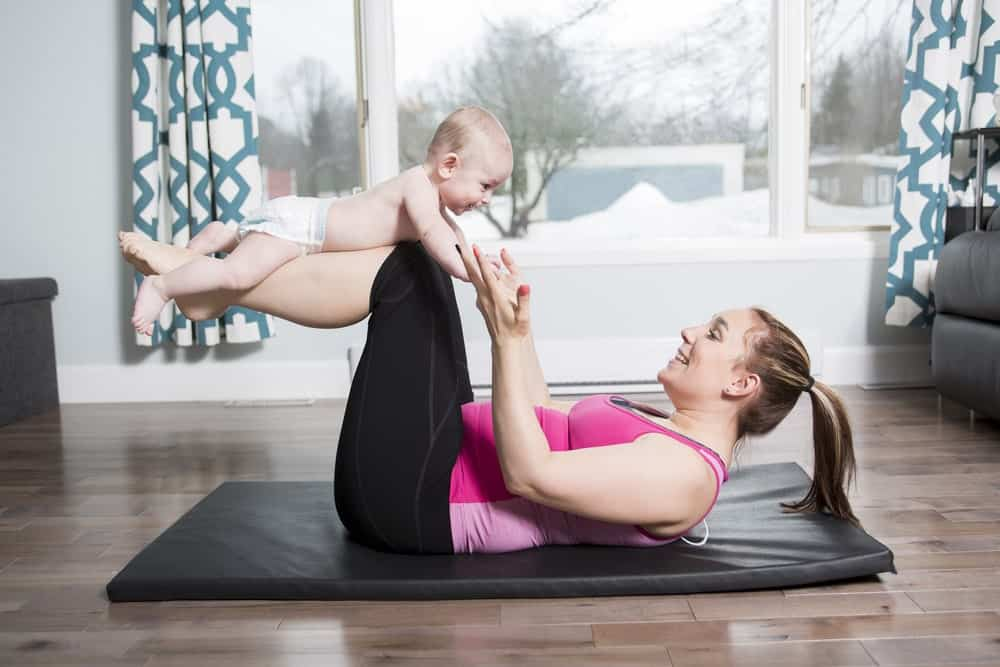 A woman lying on a Manduka yoga mat while holding a baby on her feet.