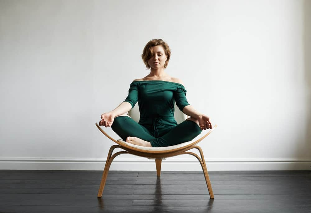 Woman sitting on a chair while meditating in a lotus position.