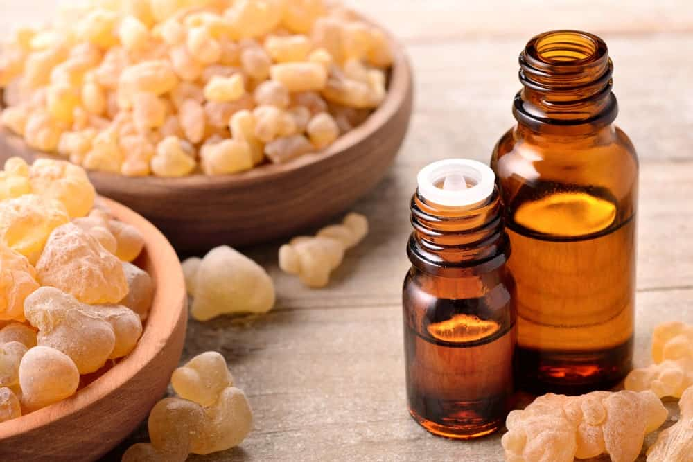 Two bowls of Frankincense and bottles of essential oil.