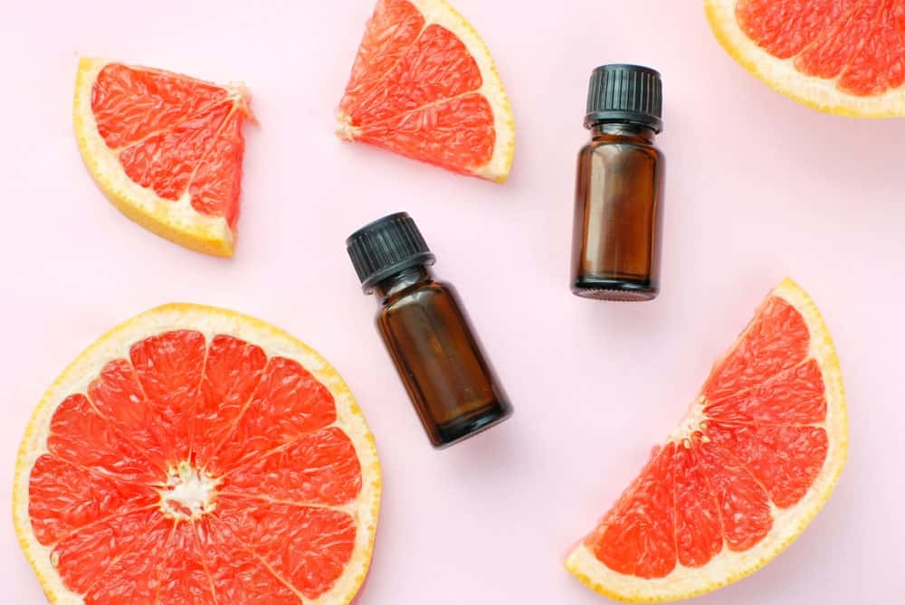 Grapefruit slices and bottles of essential oil.