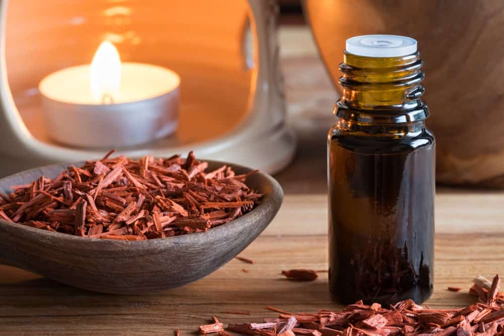 A bowl of sandalwood and a bottle of essential oil.