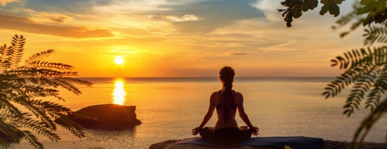 A woman practicing yoga at sunset