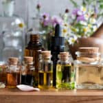 Bottles of essential oils with various herbs and flowers.