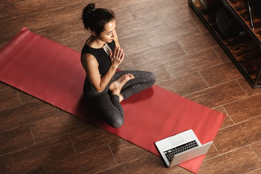 Woman practicing a yoga pose in front of an open laptop.