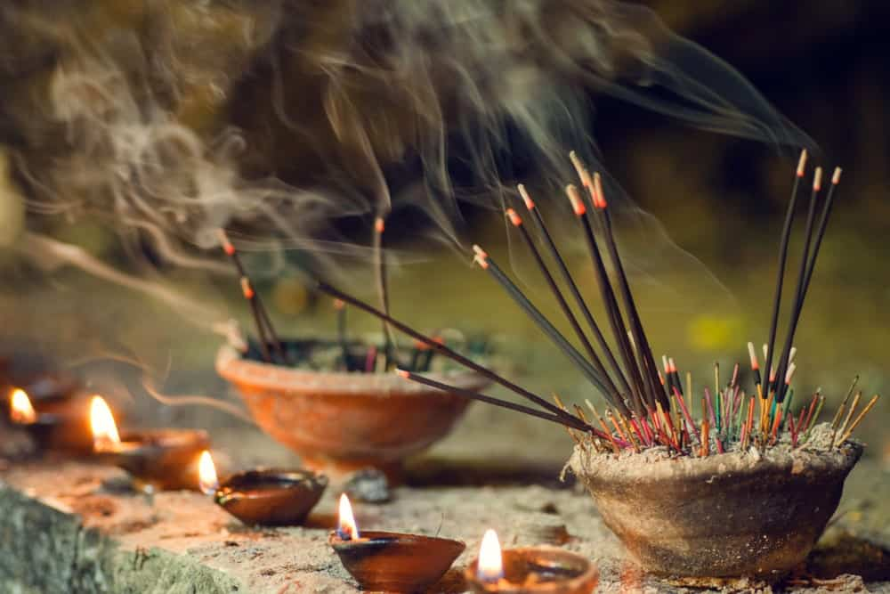 Stick incenses burning in a ceramic bowl