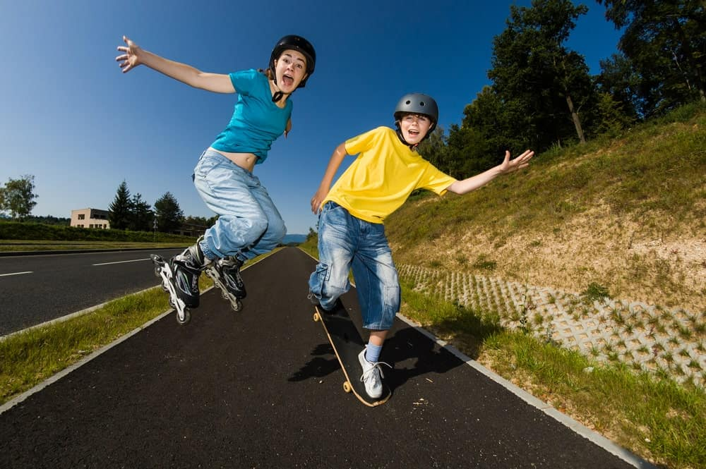 A Girl and Boy Skateboarding and Rollerblading