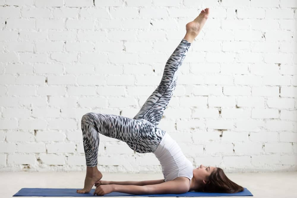 Woman practicing yoga on a blue mat.