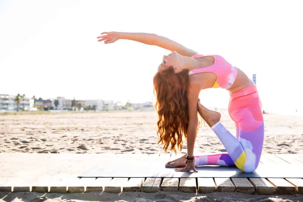 Woman in multi-colored sportswear practicing yoga at the beach.