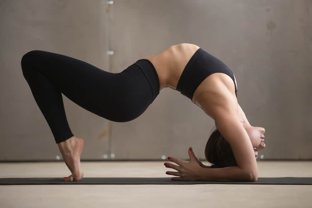 Woman in black pants and bra practicing yoga.