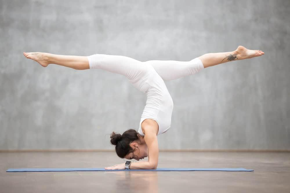 Woman in white sportswear practicing yoga.