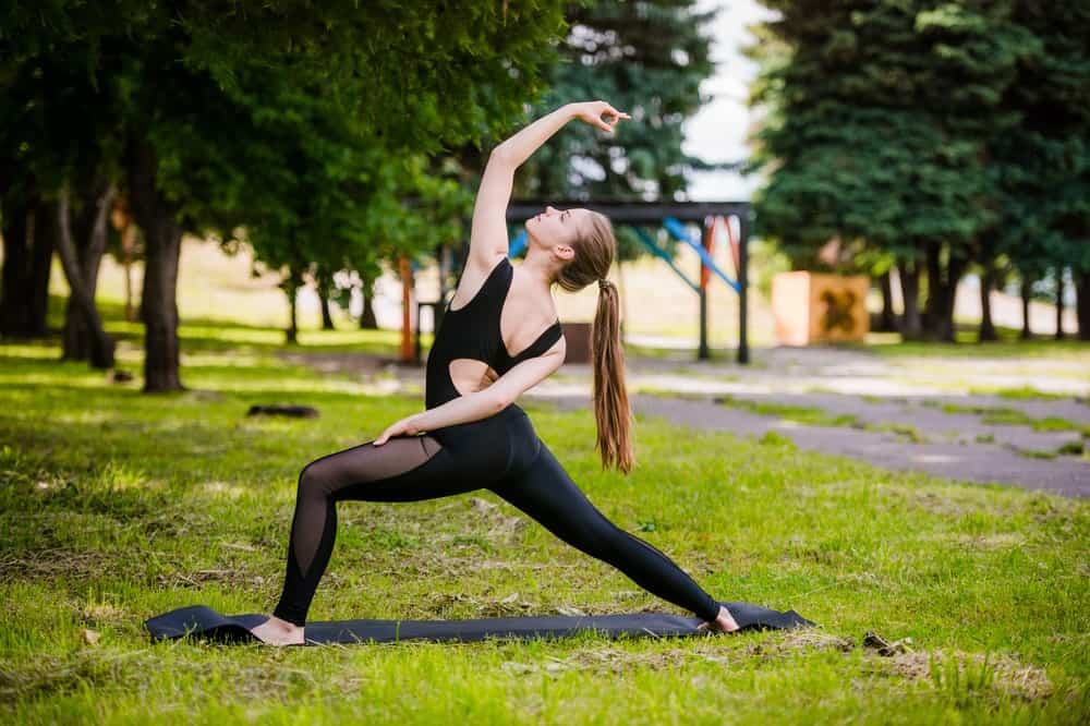 Woman practicing yoga at the park.
