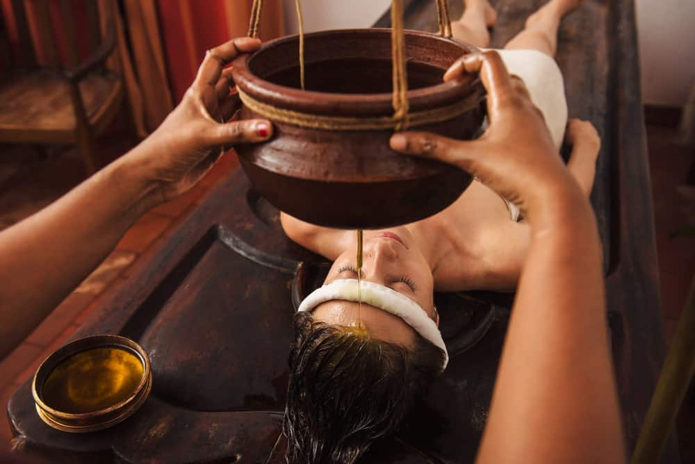 A woman having Ayurveda shirodhara treatment.