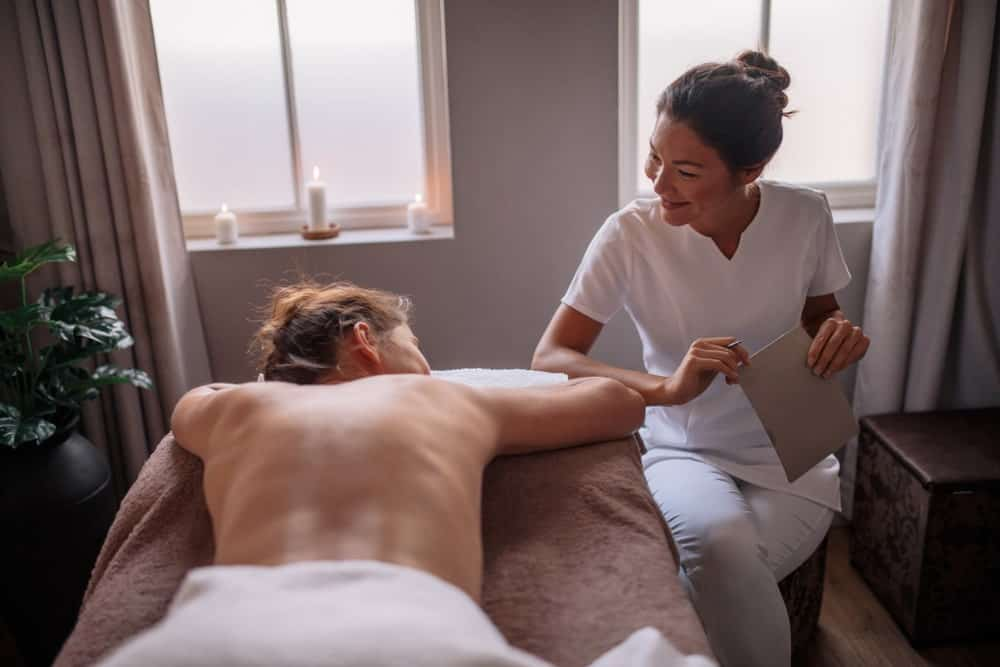 A masseuse talking with female client before the spa treatment at wellness center.